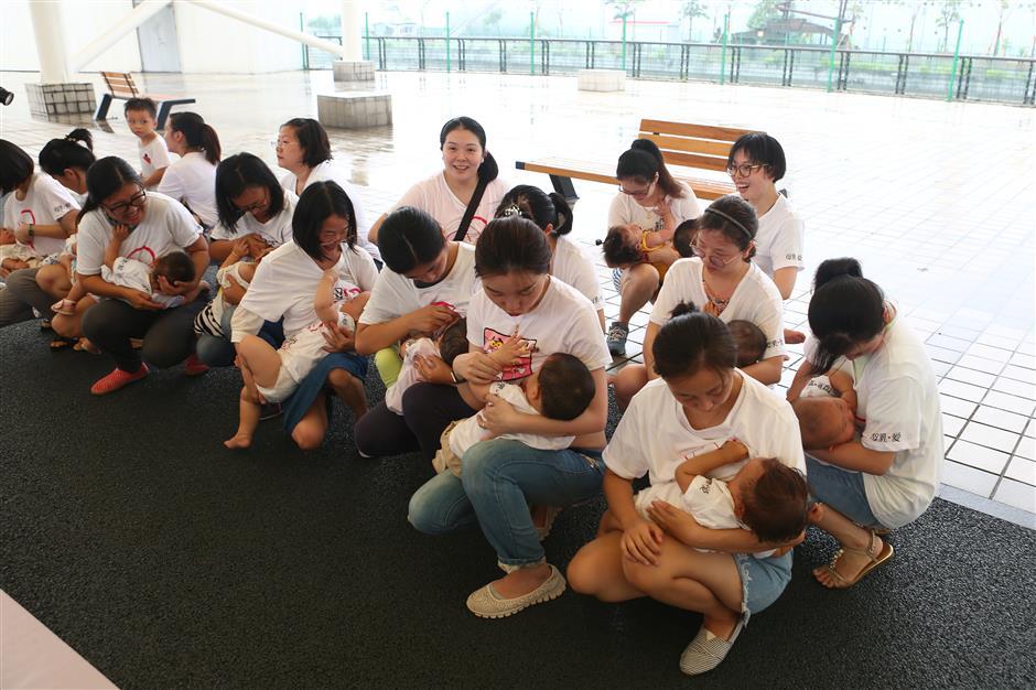 Moms nurse babies in a public breastfeeding flash mob