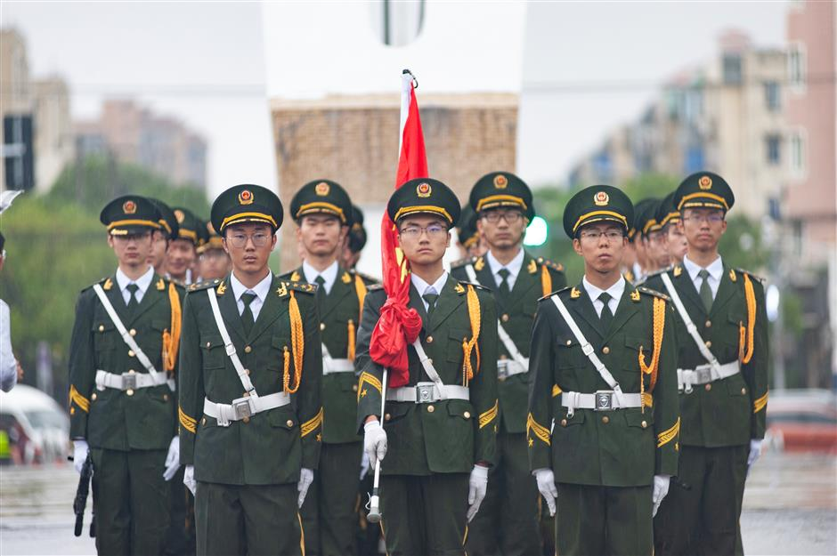 Residents brave rain to attend flag raising ceremony at Jiao Tong University