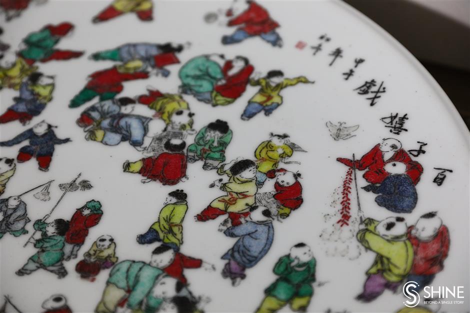 Artisan adorns plates, vases in delicate art