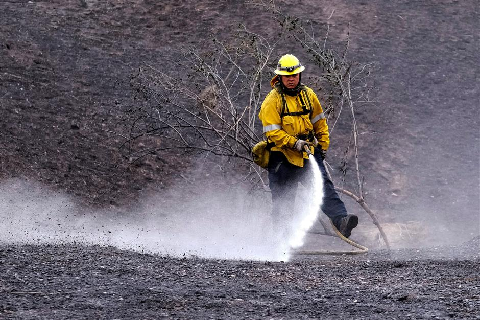 High winds reignite deadly forest fires in US west