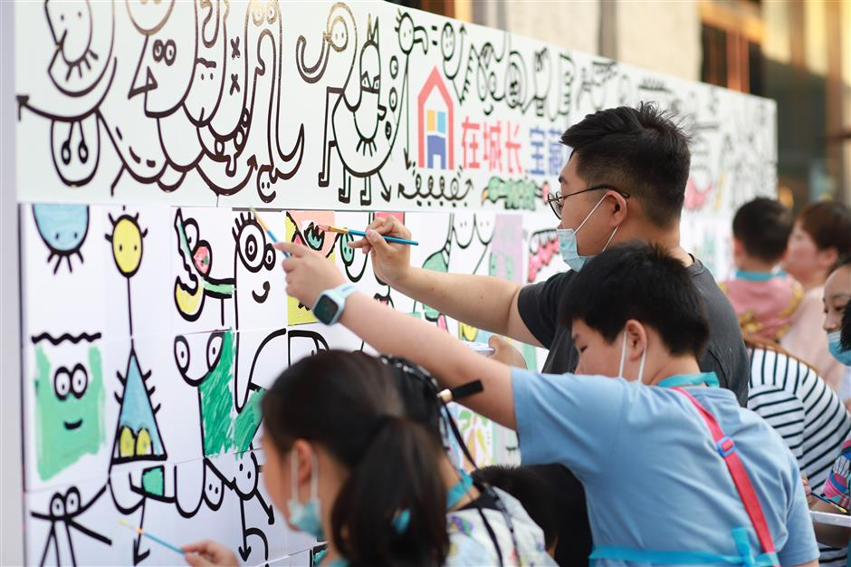 Children of migrant workers enjoy coloring in graffiti sketch